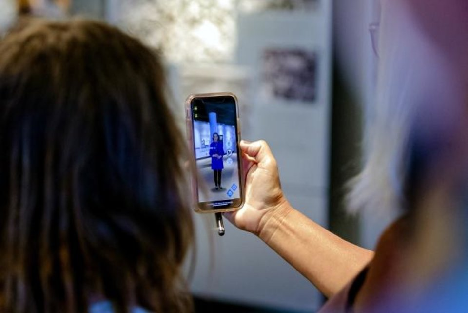 Photo -  Today's mobile phones are capable of conveying information in multiple ways. Kitty Wade, of Fort Worth, Texas, uses the augmented reality feature on her phone as she takes a tour of the Oklahoma City National Memorial Museum one day last month. [Chris Landsberger/The Oklahoman]