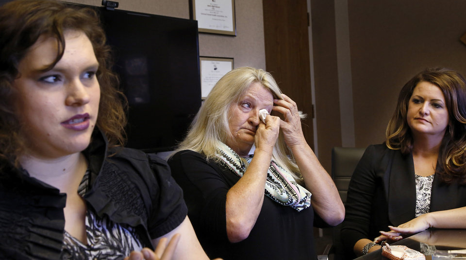 Photo -  Michael Tate Reed II's mother , Crystal Tucker, wipes tears when discussing the emotional toll her son's mental illness and his behavior have created for her family and for Reed during an interview in the office of the Mental Health Association Oklahoma in Tulsa on Wednesday, Oct. 29, 2014. Also shown are Dena Lynch, left, one of Reed's closest friends and Mindy Poor, Reed's sister. Reed has suffered from serious mental illness for at least two years, his family says. Reed hasn't ever been formally diagnosed, but mental health experts have told the family that Reed likely has schizoaffective disorder, a brain disease that is a mix of schizophrenia and bipolar disorder. Reed is at a mental health facility, and his family and friends hope he doesn't have to spend time in prison when they say he's suffering from a mental illness and is not a terrorist or Satanist, as some have called him after he admitted to law officers that he drove his vehicle onto the lawn of the state Capitol and crashed into the Ten Commandments monument, toppling it from its base and breaking it into several pieces. Photo by Jim Beckel, The Oklahoman   Jim Beckel -  THE OKLAHOMAN