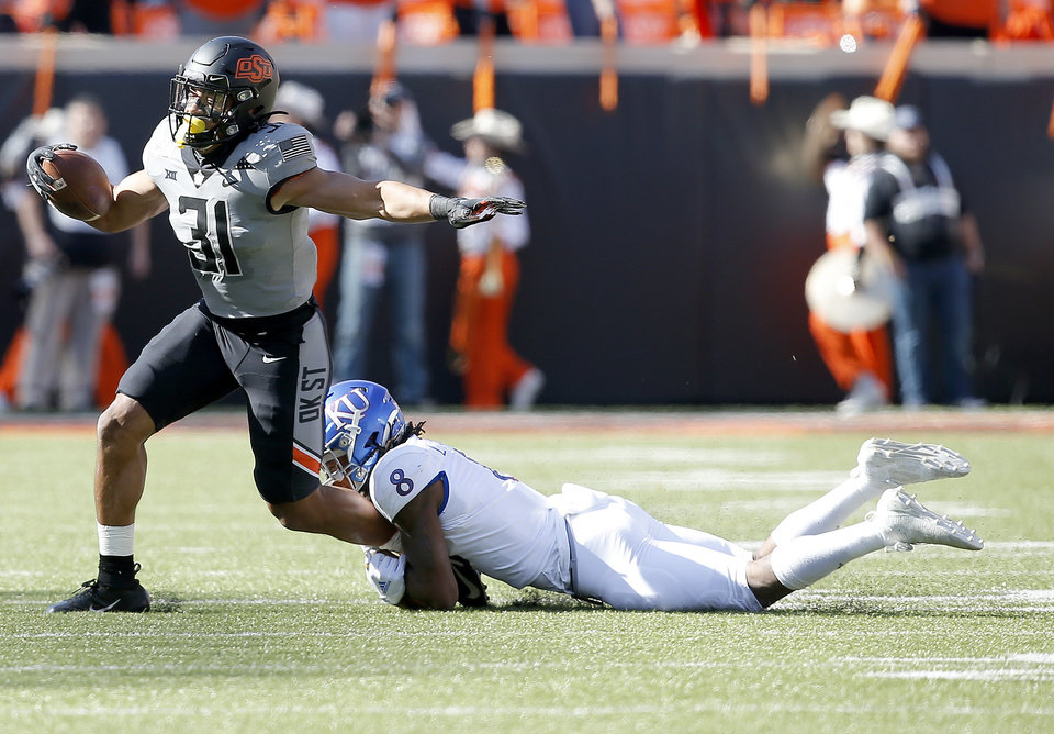 Photo - Kolby Harvell-Peel (31) runs after an interception as Kansas's Kwamie Lassiter II (8) defends in the second quarter during the college football game between the Oklahoma State University Cowboys and the Kansas Jayhawks at Boone Pickens Stadium in Stillwater, Okla., Saturday, Nov. 16, 2019. OSU won 31-13. [Sarah Phipps/The Oklahoman]