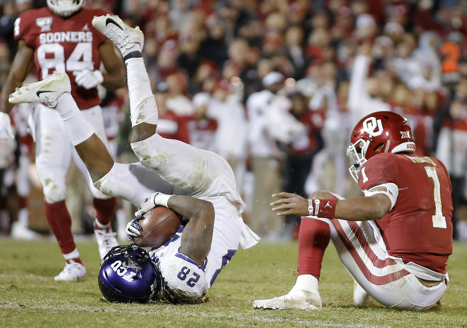 Photo - Nook Bradford (28) of TCU comes up with the ball after taking it from Oklahoma's Jalen Hurts (1) during an NCAA football game between the University of Oklahoma Sooners (OU) and the TCU Horned Frogs at Gaylord Family-Oklahoma Memorial Stadium in Norman, Okla., Saturday, Nov. 23, 2019. Oklahoma won 28-24. [Bryan Terry/The Oklahoman]
