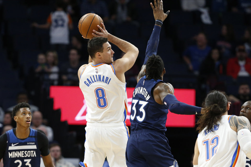 Photo - Oklahoma City Thunder's Danilo Gallinari, left, of Italy looks to pass as Minnesota Timberwolves' Robert Covington defends in the first half of an NBA basketball game Monday, Jan. 13, 2020, in Minneapolis. (AP Photo/Jim Mone)