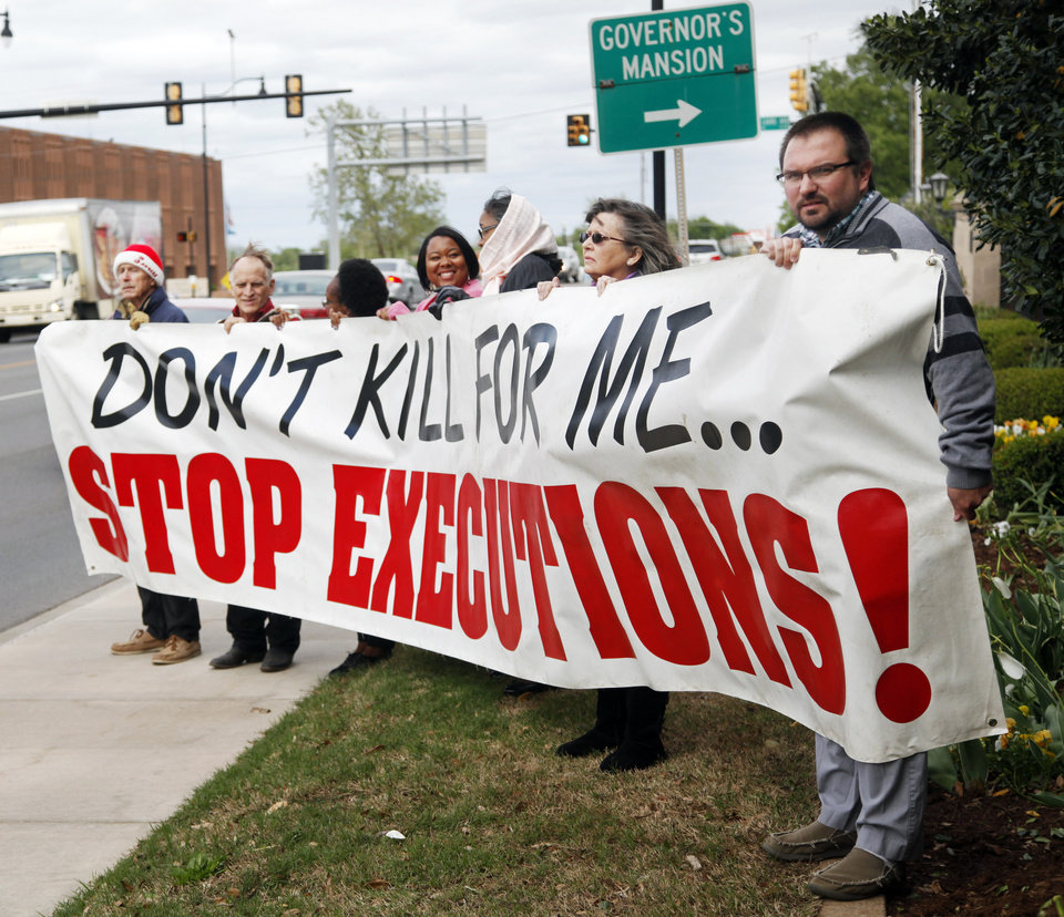 Photo - Protesters hold a sign to protest at the Governor's Mansion over the execution of two inmates. The protest was held in Oklahoma City on Tuesday, April 29, 2014 Photo by KT King, The Oklahoman