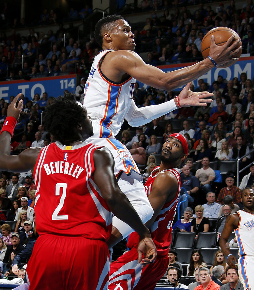 Photo - Oklahoma City's Russell Westbrook (0) goes between Houston's Patrick Beverley (2) and Corey Brewer (33)  during an NBA basketball game between the Oklahoma City Thunder and the Houston Rockets at Chesapeake Energy Arena in Oklahoma City, Friday, Jan. 29, 2016. Photo by Bryan Terry, The Oklahoman