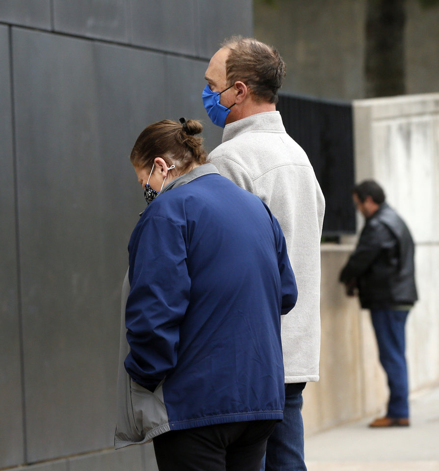 Photo - Zena Dater, left, and Steve Dater, pause for 168 seconds of silence beginning at 9:02 a.m. outside of the Oklahoma City National Memorial and Museum on the 25th anniversary of the bombing of the Alfred P. Murrah Federal Building, in Oklahoma City, Sunday, April 19, 2020. The Daters knew bombing victim Linda McKinney. The memorial remains closed and did not hold a live remembrance ceremony because of the coronavirus pandemic. The 168 seconds of silence is to honor the 168 victims of the bombing. [Nate Billings/The Oklahoman]