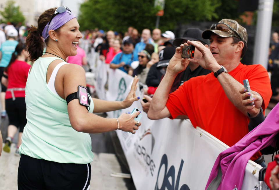 Photo - Mike McGee of Chanute, Kansas takes a picture of his daughter Amy Almond as she starts the 14th Annual Oklahoma City Memorial Marathon in Oklahoma City, Sunday, April 27, 2014. The marathon was delayed over two hours beyond it's original start time of 6 a.m. Photo by KT King/The Oklahoman