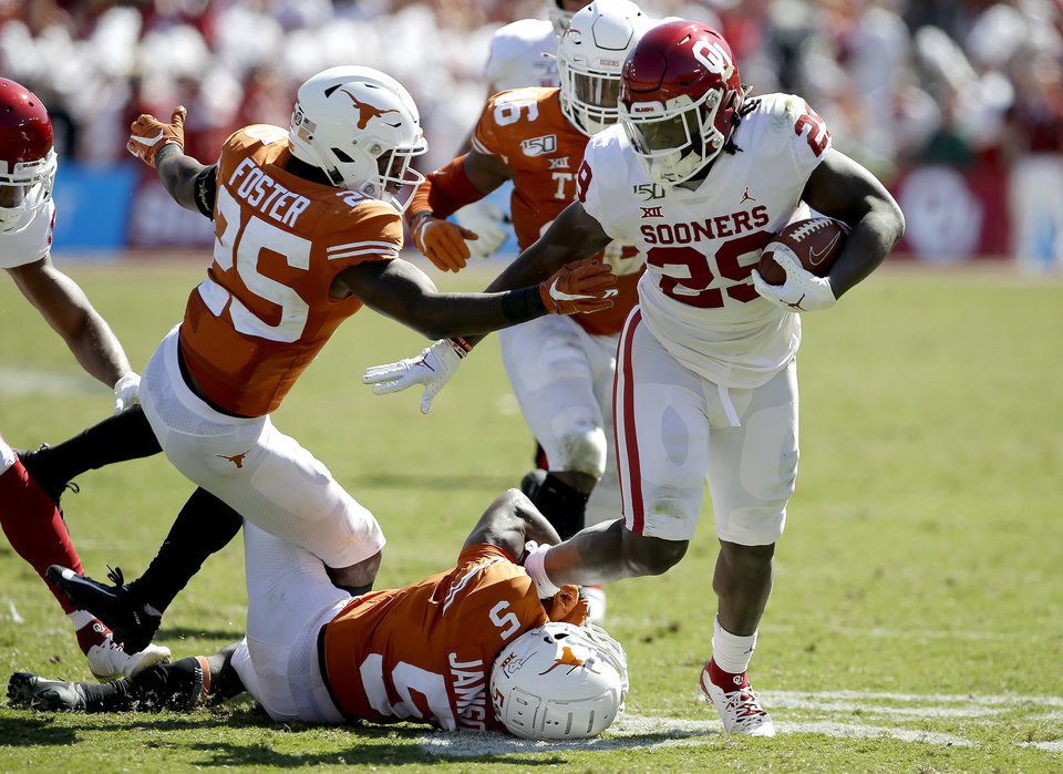 Photo - Oklahoma running back Rhamondre Stevenson (29) runs past Texas defensive back B.J. Foster (25) and defensive back D'Shawn Jamison (5) during the Red River Showdown college football game between the University of Oklahoma Sooners (OU) and the Texas Longhorns (UT) at Cotton Bowl Stadium in Dallas, Saturday, Oct. 12, 2019. Oklahoma won 34-27. [Bryan Terry/The Oklahoman]