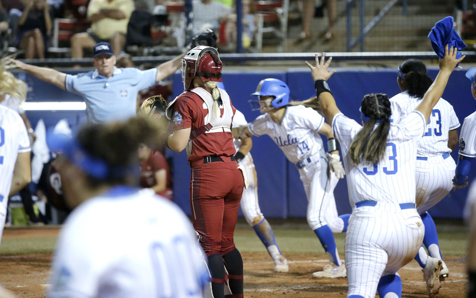Photo - UCLA celebrates the Women's College World Series championship around Oklahoma's Lynnsie Elam (22) in the 7th inning at USA Softball Hall of Fame Stadium in Oklahoma City, Tuesday, June 4, 2019. [Sarah Phipps/The Oklahoman]