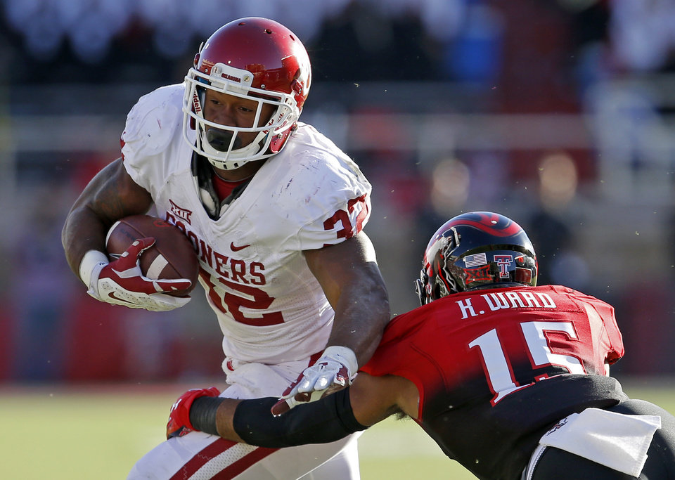 Photo - Oklahoma's Keith Ford (21) runs past Texas Tech's Keenon Ward (15) during a college football game between the University of Oklahoma Sooners (OU) and the Texas Tech Red Raiders at Jones AT&T Stadium in Lubbock, Texas, Saturday, November 15, 2014.  Photo by Bryan Terry, The Oklahoman