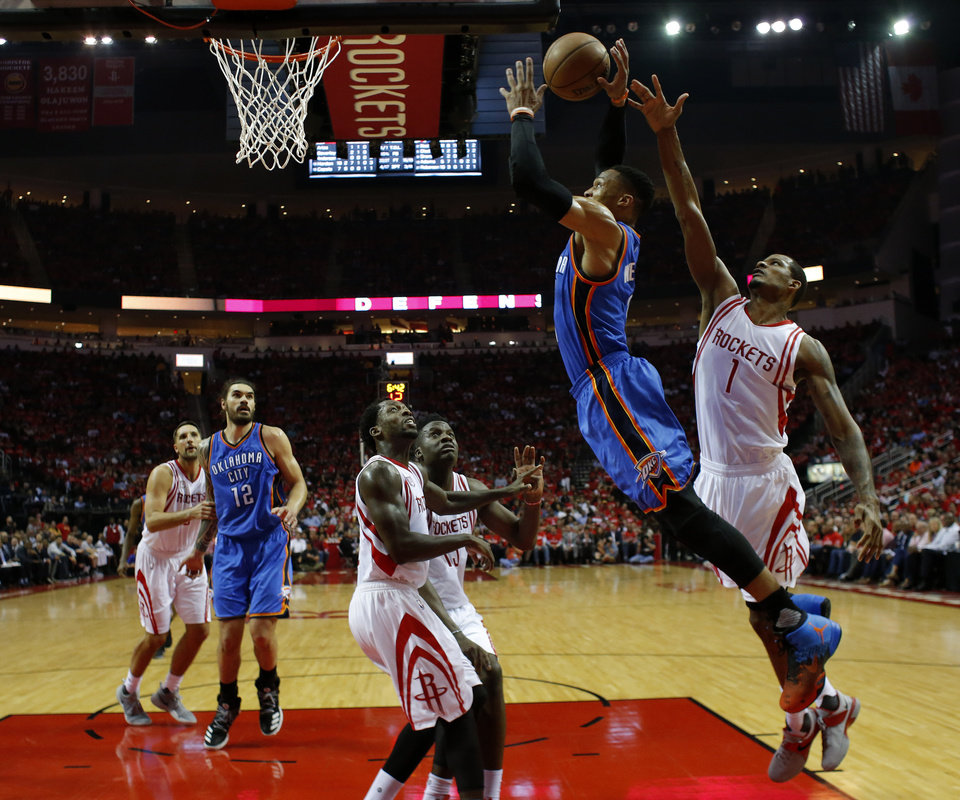 Photo - Oklahoma City's Russell Westbrook (0) goes to the basket as Houston's Trevor Ariza (1) defends during Game 2 in the first round of the NBA playoffs between the Oklahoma City Thunder and the Houston Rockets in Houston, Texas,  Wednesday, April 19, 2017.  Photo by Sarah Phipps, The Oklahoman