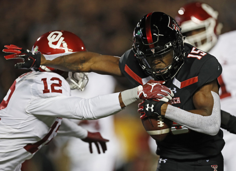 Photo - Texas Tech's Vaughnte Dorsey (15) breaks a tackle by Oklahoma's A.D. Miller (12) after intercepting a pass during the first half of an NCAA college football game Saturday, Nov. 3, 2018, in Lubbock, Texas. (AP Photo/Brad Tollefson)