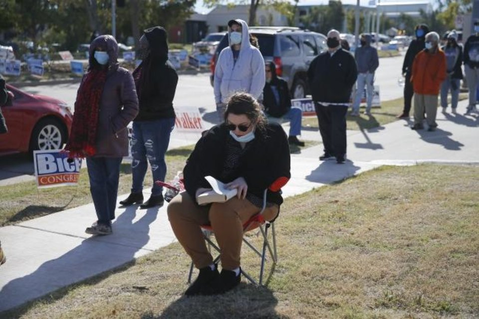 Photo -  Katie Booth-Wlodarczyk reads a book as she waits in line with other voters on Saturday outside the Oklahoma County Election Board in Oklahoma City. [Bryan Terry/The Oklahoman]