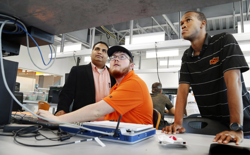 Photo -  Seniors Bradley Ingram, seated, and Jarrett Talbott work on an assignment in the new mechanical engineering technology lab at Oklahoma State University as assistant professor Hitesh Vora observes. [Photo by Jim Beckel, The Oklahoman]