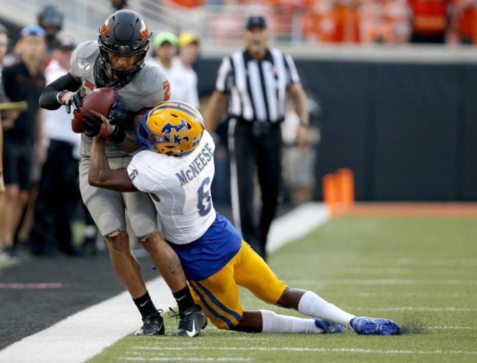 Photo -  Oklahoma State's Tylan Wallace, left, comes down with a pass over McNeese State defensive back Calum Foster Saturday at Boone Pickens Stadium. [Sarah Phipps/The Oklahoman]