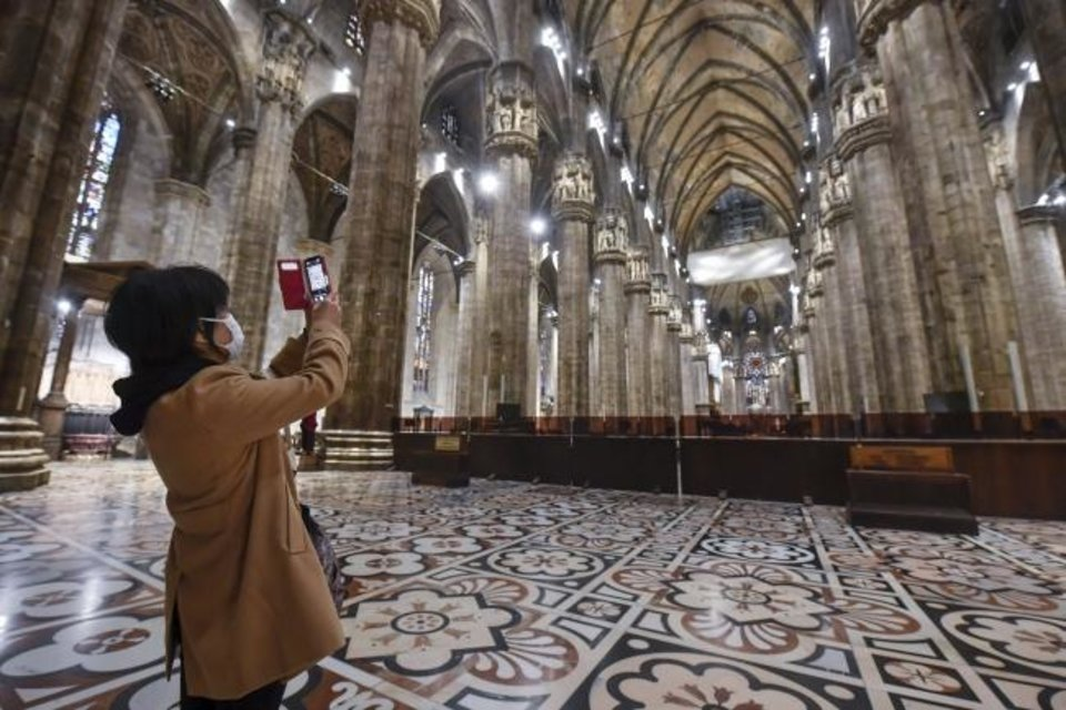 Photo -  A tourist wearing a face mask takes pictures inside the Duomo Gothic cathedral as it reopened to the public on March 2 after being closed due to the COVID-19 virus outbreak in Milan in northern Italy. [Claudio Furlan/LaPresse/AP]