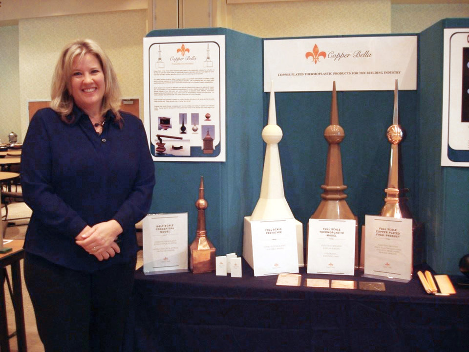 Photo - Copper Bella owner Teri Ward stands beside her company's exhibit during the Wes Watkins New Product and Process Fair.  Photo provided by Copper Bella