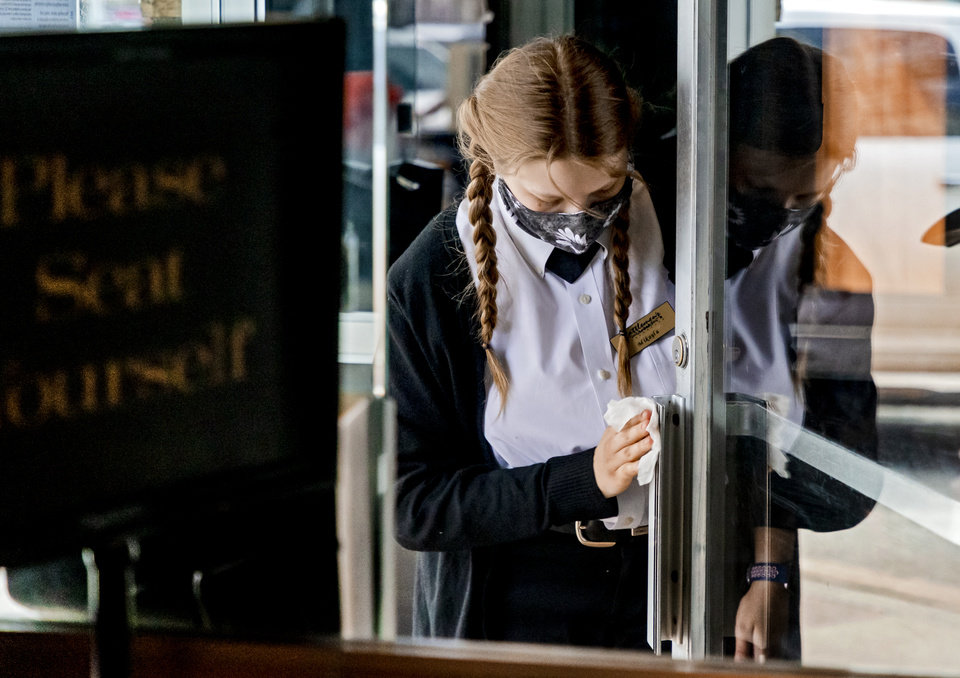 Photo - Hostess Mikayla Singley sanitizes the door handle for customers as they arrive for lunch at Cattlemen's Steakhouse in Oklahoma City, Okla. on Friday, May 1, 2020. Cattlemen's and other restaurants begin their gradual reopening on Friday after being closed due to the Coronavirus Pandemic.[Chris Landsberger/The Oklahoman]