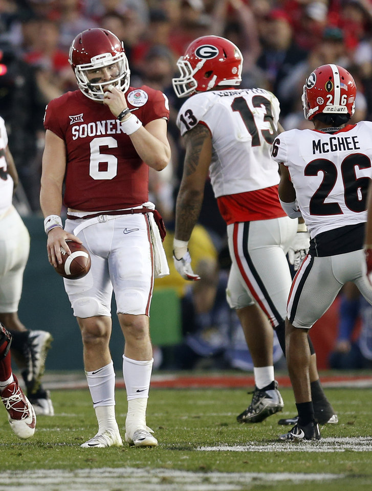 Photo - Oklahoma's Baker Mayfield (6) stands next to Georgia's Jonathan Ledbetter (13) and Tyrique McGhee (26) after being sacked in the third quarter during the Rose Bowl Game, a College Football Playoff Semifinal, between the Oklahoma Sooners (OU) and Georgia Bulldogs (UGA) at the Rose Bowl in Pasadena, California, Monday, Jan. 1, 2018. Georgia won 54-48 in double overtime. Photo by Nate Billings, The Oklahoman