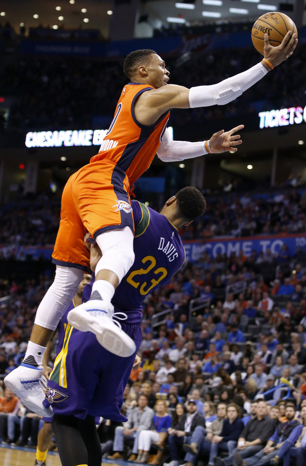 Photo - Oklahoma City's Russell Westbrook (0) is fouled by New Orleans' Anthony Davis (23) as he goes to the basket during the NBA basketball game between the Oklahoma City Thunder and the New Orleans Pelicans at the Chesapeake Energy Arena, Saturday, Feb. 25, 2017.  Photo by Sarah Phipps, The Oklahoman