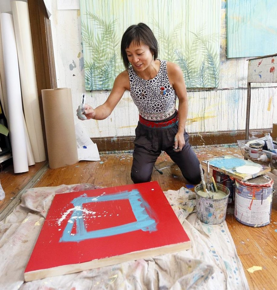 Photo - Local artist Denise Duong paints in her home studio in Oklahoma City, Thursday, May 16, 2019. [The Oklahoman Archives]