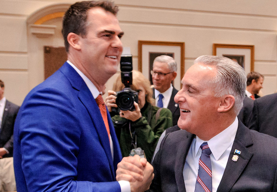 Photo -  State Sen. Paul Rosino, right, shakes hands with Gov. Kevin Stitt.