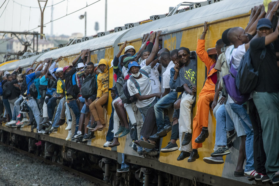 Photo -  FILE - In this Monday, March 16, 2020 file photo, train commuters hold on to the side of an overcrowded passenger train in Soweto, South Africa. Up to 150 million people could slip into extreme poverty, living on less than $1.90 a day, by late next year depending on how badly economies shrink during the COVID-19 pandemic, the World Bank said Wednesday, Oct. 7, 2020 in an outlook grimmer than before. (AP Photo/Themba Hadebe, File)