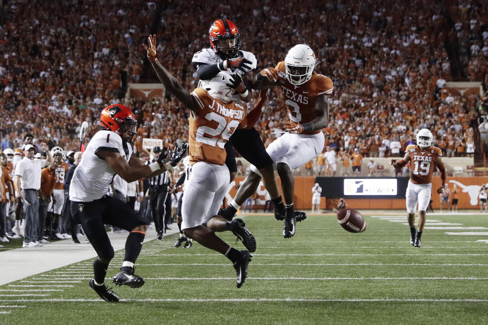 Photo - Texas defensive back Josh Thompson (29) and defensive back Jalen Green (3) break up a pass intended for Oklahoma State wide receiver Tylan Wallace (2) during the first half of an NCAA college football game Saturday, Sept. 21, 2019, in Austin, Texas. (AP Photo/Eric Gay)