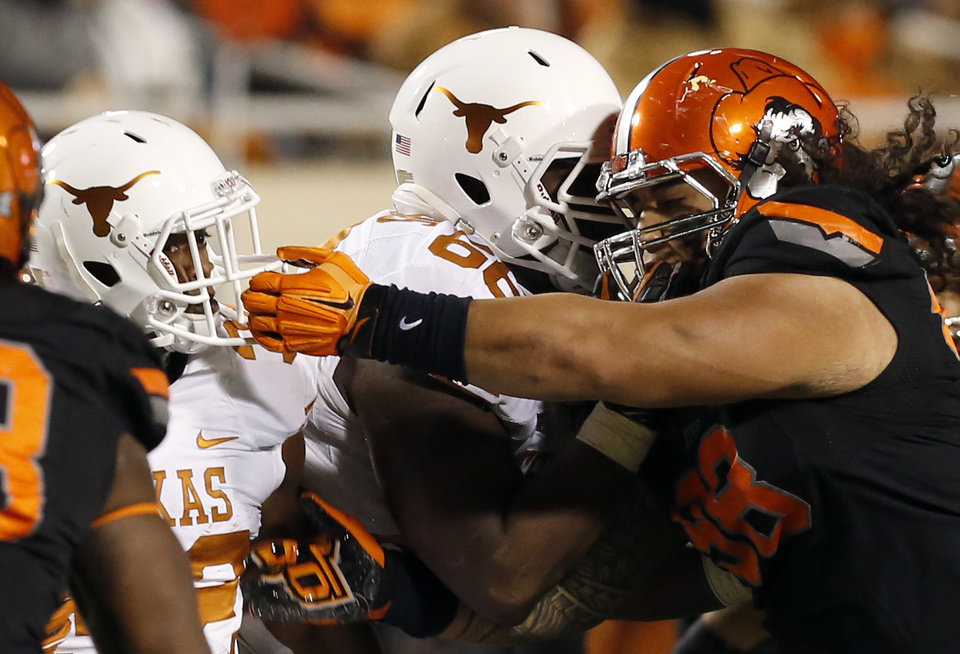 Photo - Oklahoma State's Ofa Hautau (98) commits a face mask on Texas Johnathan Gray (32) during the college football game between the Oklahoma State University Cowboys (OSU) the University of Texas Longhorns (UT) at Boone Pickens Staduim in Stillwater, Okla. on Saturday, Nov. 15, 2014.  Photo by Sarah Phipps, The Oklahoman