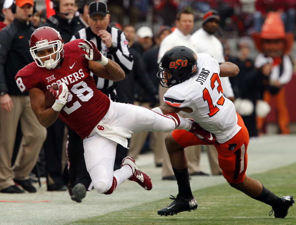 Photo - Cowboy's Jordan Sterns (13) usher Sooner's Alex Ross (28) out of bounds during a Bedlam college football game between the University of Oklahoma Sooners (OU) and the Oklahoma State Cowboys (OSU) at Gaylord Family-Oklahoma Memorial Stadium in Norman, Okla., on Saturday, Dec. 6, 2014. Photo by Steve Sisney, The Oklahoman