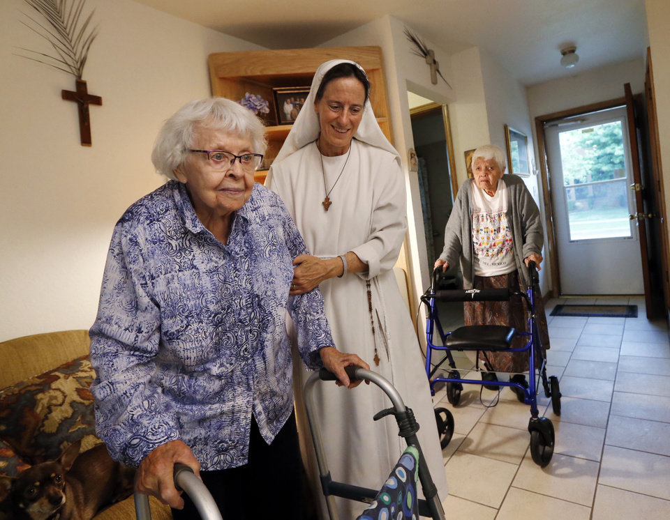 Photo -  Sister Maria Faulkner helps Annabelle Miller to the piano while Lucy Hooper, at right, looks on at the Gospel of Life Dwelling in south Oklahoma City. [Photo by Steve Sisney, The Oklahoman]