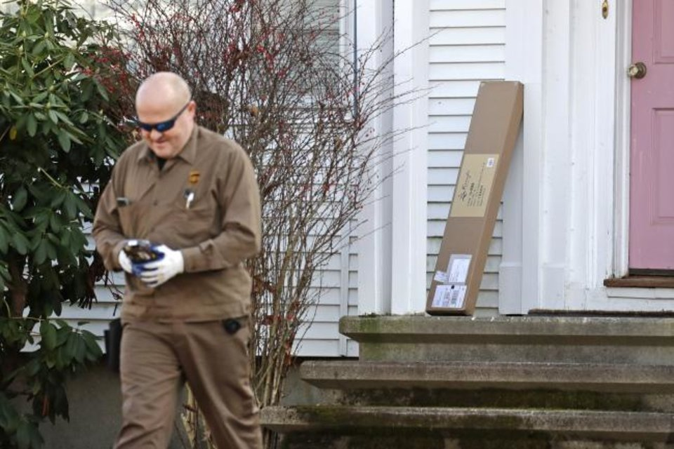 Photo -  A UPS man leaves after delivering a package to a residence in North Andover, Mass.  [AP PHOTO]