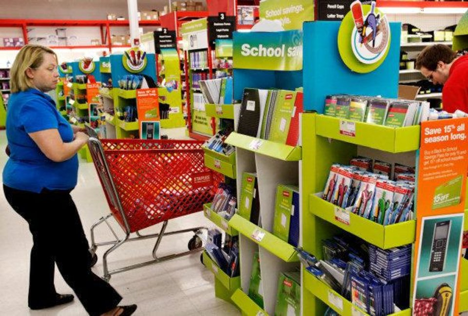 Photo - A shopper browses school supply selection as a store worker, right,  re-stocks merchandise.  School supplies at Staples near I-240 and Walker in south Oklahoma City, Wednesday,  July 13,  2011.      Photo by Jim Beckel, The Oklahoman ORG XMIT: KOD