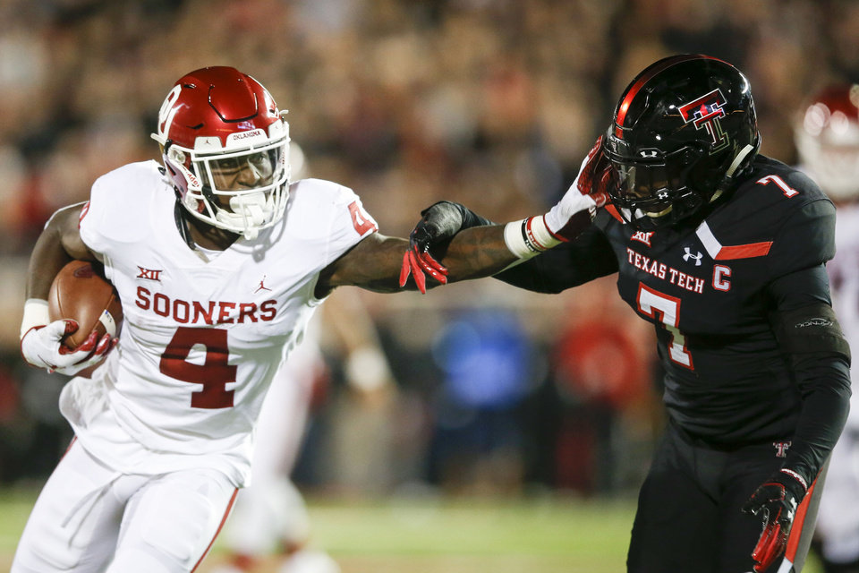 Photo - Oklahoma Sooners running back Trey Sermon (4) stiff arms Texas Tech Red Raiders defensive back Jah'Shawn Johnson (7)during the NCAA football game between the Texas Tech Red Raiders and the Oklahoma Sooners at Jones AT&T Stadium in Lubbock, Texas on Saturday, November 03, 2018. IAN MAULE/Tulsa World