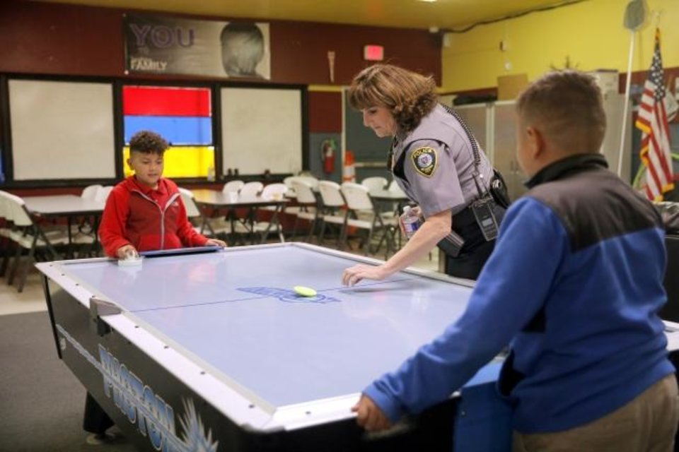 Photo -  Sgt. Suzanne Montgomery starts a game of air hockey between Oleksie Torres, 10, left, and Wzquiel Torres, 11, during the Police Athletic League's after-school program. [Bryan Terry/The Oklahoman]