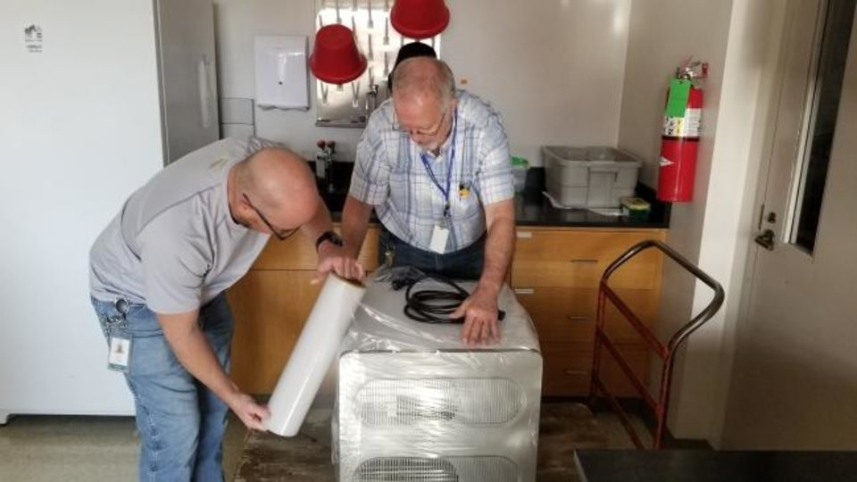 Photo -  Sean Turner and Mike Austin prepare two machines to be moved from the Oklahoma Medical Research Foundation to OU Health Sciences Center. The two machines are expected to greatly expedite COVID-19 testing. [Provided]