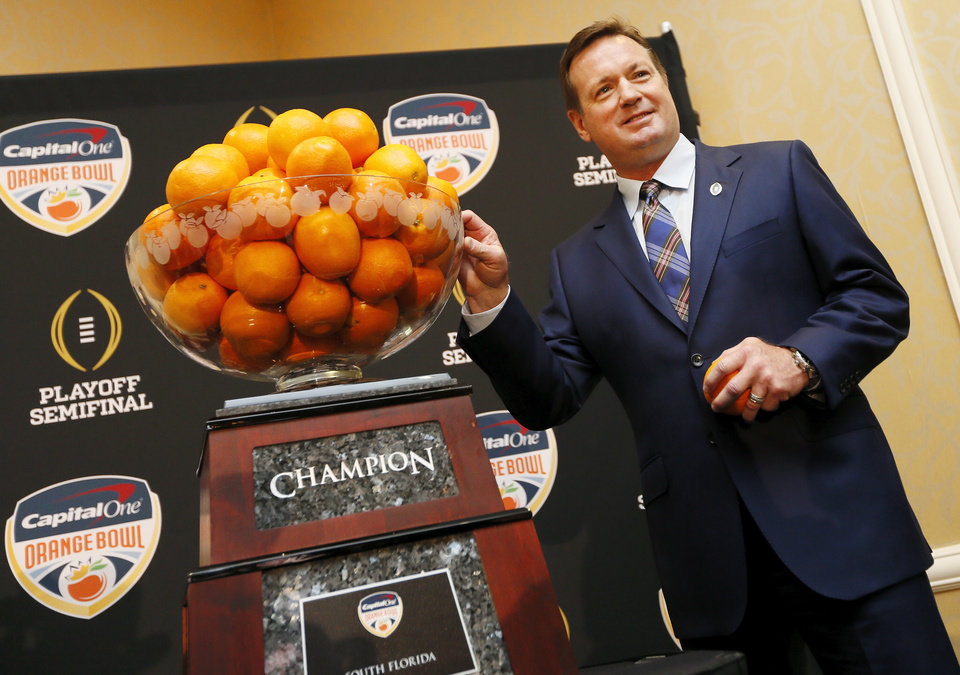 Photo - OU coach Bob Stoops poses for photos with the championship trophy for the Capital One Orange Bowl, a College Football Playoff Semifinal game, during a news conference at the Renaissance Fort Lauderdale Cruise Port Hotel in Fort Lauderdale, Florida, Wednesday, Dec. 30, 2015. The Oklahoma Sooners will play the Clemson Tigers on News Year's Eve. Photo by Nate Billings, The Oklahoman