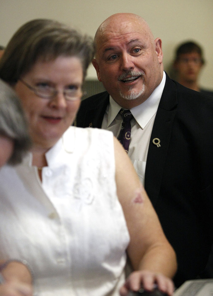 Photo - Toby Jenkins (right), executive director of Oklahomans for Equality, smiles as Sharon Baldwin (not pictured) and Mary Bishop (left), two Tulsa women at the center of a gay marriage case that was appealed to the Supreme Court, accept their marriage license on Monday, October 6, 2014 at the Tulsa County Courthouse in Tulsa, Okla. MATT BARNARD/Tulsa World