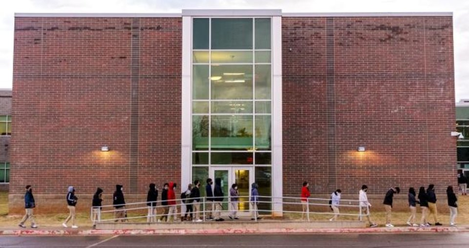 Photo -  Students wait in line to return to class at U.S. Grant High School in Oklahoma City on Nov. 10. Three days later, the district shut down upon Oklahoma County reaching the Red Level of community COVID-19 spread. [Chris Landsberger/The Oklahoman]