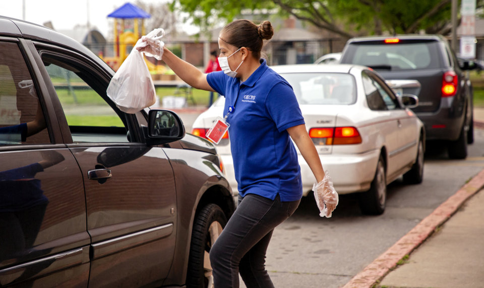Photo - Maribel Sierra brings out a meal as cars line up for distribution of meals and distant learning packets at Prairie Queen Elementary in Oklahoma City, Okla. on Monday, April 6, 2020. Oklahoma City Public Schools and other districts across the state began their first day of handing out the distant learning packets.    [Chris Landsberger/The Oklahoman]