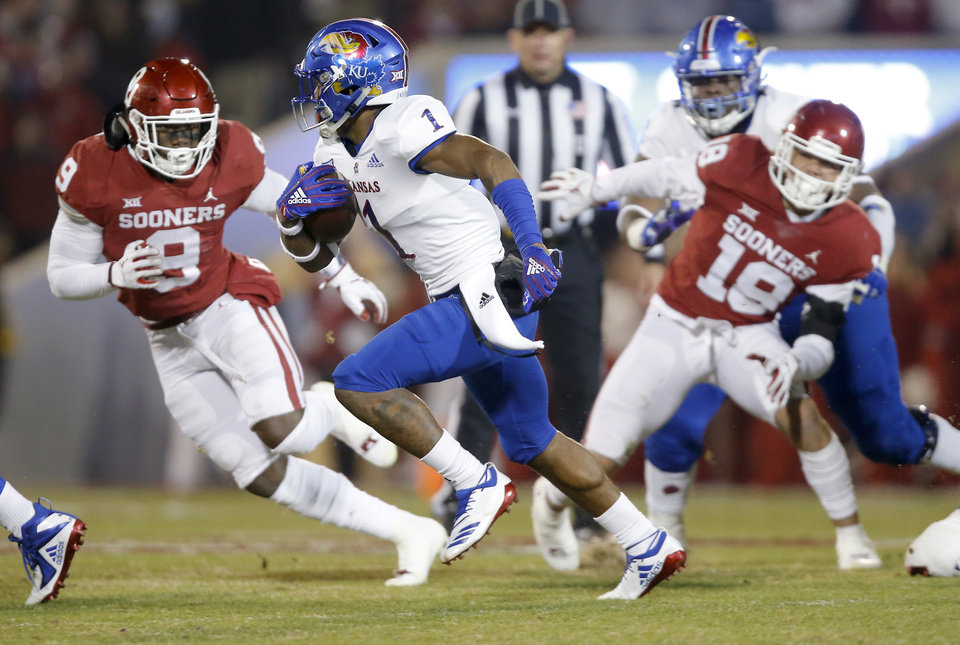 Photo - Kansas' Pooka Williams Jr. (1) carries the ball past Oklahoma's Kenneth Murray (9) and Oklahoma's Curtis Bolton (18) during a college football game between the University of Oklahoma Sooners (OU) and the Kansas Jayhawks (KU) at Gaylord Family-Oklahoma Memorial Stadium in Norman, Okla., Saturday, Nov. 17, 2018. Photo by Bryan Terry, The Oklahoman