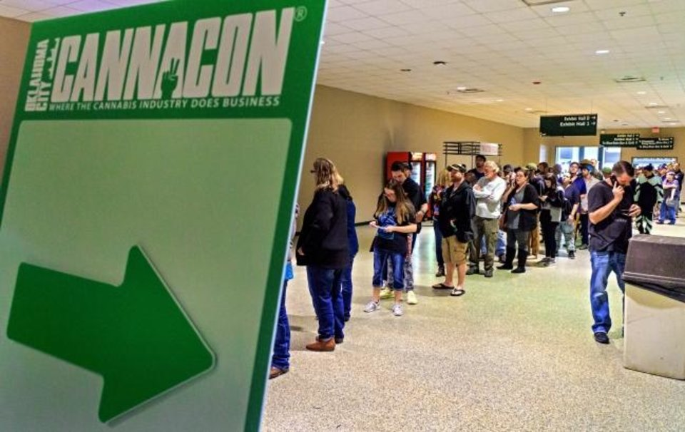 Photo -  People line up Thursday to attend the Oklahoma City CannaCon at the Cox Convention Center. [CHRIS LANDSBERGER/THE OKLAHOMAN]
