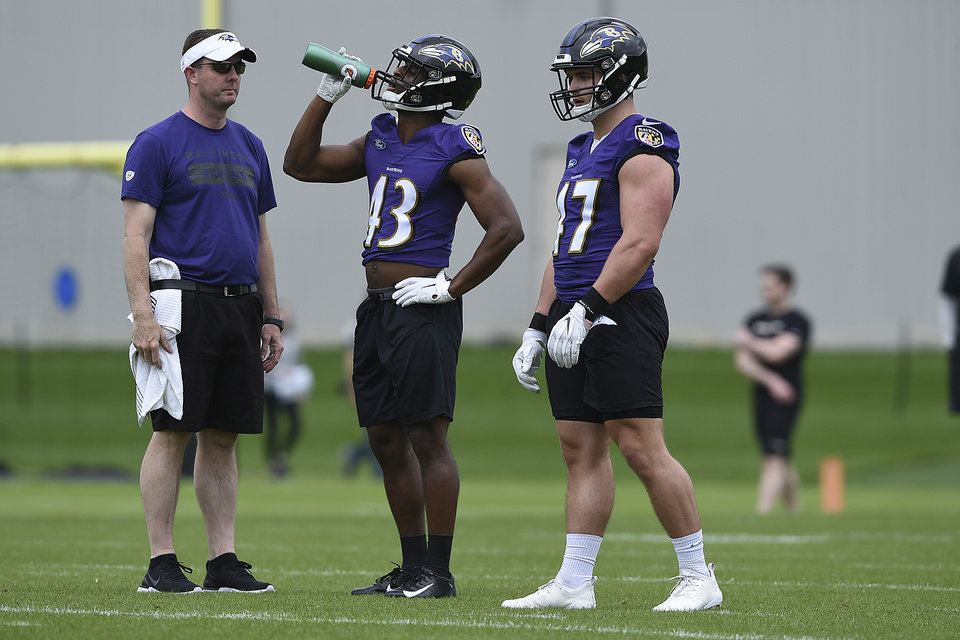 Photo - Baltimore Ravens rookie running back Justice Hill, center, drinks water during NFL Football rookie camp, Saturday, May 4, 2019 in Owings Mills, Md.(AP Photo/Gail Burton)