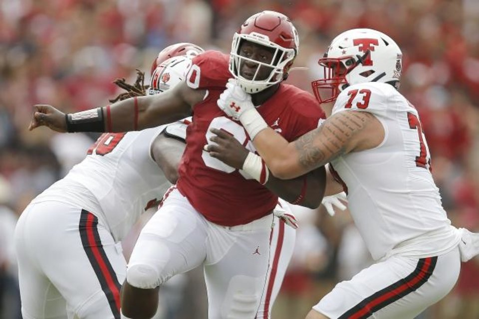 Photo -  Oklahoma defensive lineman Neville Gallimore, center, tries to get past Texas Tech's Dawson Deaton during the Sept. 28 game at Owen Field. [Bryan Terry/The Oklahoman]