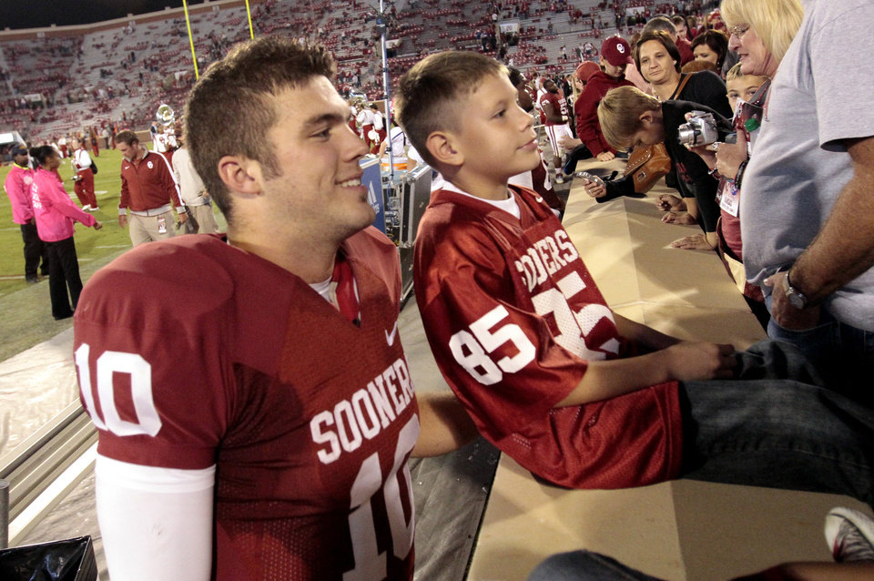 Photo - Blake Bell (10) poses with fans after the college football game where the University of Oklahoma Sooners (OU) defeated the University of Kansas Jayhawks (KU) 52-7 at Gaylord Family-Oklahoma Memorial Stadium in Norman, Okla., on Saturday, Oct. 20, 2012. Photo by Steve Sisney, The Oklahoman