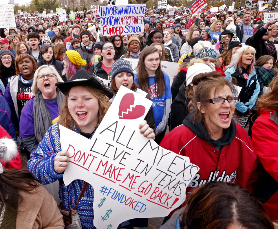 Photo -  Kalee Morales, Piedmont teacher, holds a Texas sign as Oklahoma teachers hold a rally at the State Capitol on Monday in Oklahoma City. [Photo by Steve Sisney, The Oklahoman]