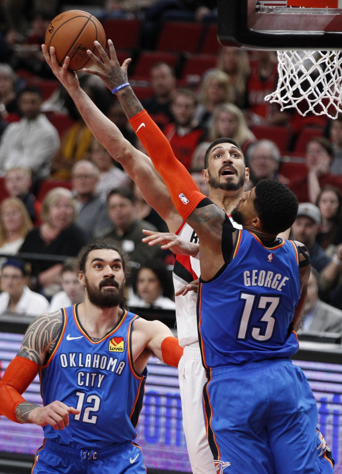Photo - Portland Trail Blazers center Enes Kanter, center, shoots as Oklahoma City Thunder center Steven Adams, left, and forward Paul George, right, defend during the second half of Game 1 of a first-round NBA basketball playoff series in Portland, Ore., Sunday, April 14, 2019. (AP Photo/Steve Dipaola)