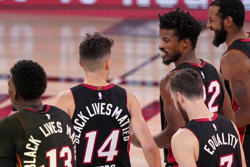 Photo - Miami Heat's Bam Adebayo (13), from left, Tyler Herro (14), Goran Dragic, right front, Jimmy Butler, from second right and Andre Iguodala, right, walks off the court celebrating their 112-109 win in Game 4 of an NBA basketball Eastern Conference final against the Boston Celtics on Wednesday, Sept. 23, 2020, in Lake Buena Vista, Fla. (AP Photo/Mark J. Terrill)
