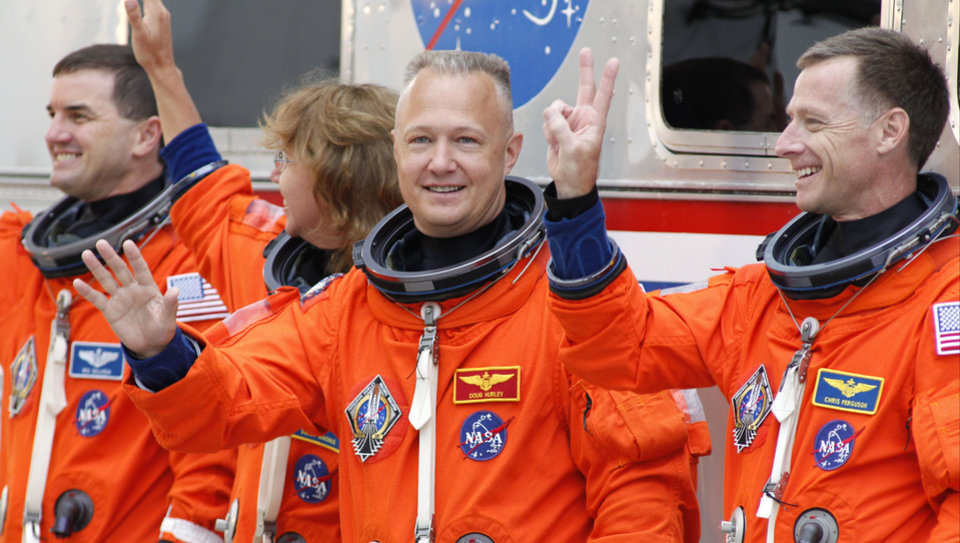 Photo -  FILE - In this Friday, July 8, 2011 file photo, space shuttle Atlantis astronauts, from left, mission specialists Rex Walheim and Sandy Magnus, pilot Doug Hurley and commander Chris Ferguson, wave as they leave the operations and check-out building on the way to the pad at the Kennedy Space Center in Cape Canaveral, Fla. Atlantis is the 135th and final space shuttle launch for NASA. (AP Photo/Terry Renna)
