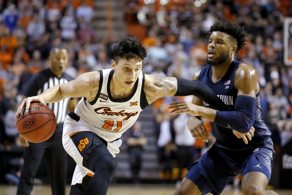 Photo - Oklahoma State's Lindy Waters III (21) goes past Georgetown's Jagan Mosely (4) during a college basketball game between the Oklahoma State University Cowboys (OSU) and the Georgetown Hoyas at Gallagher-Iba Arena in Stillwater, Okla., Wednesday, Dec. 4, 2019. Georgetown won 84-71. [Bryan Terry/The Oklahoman]