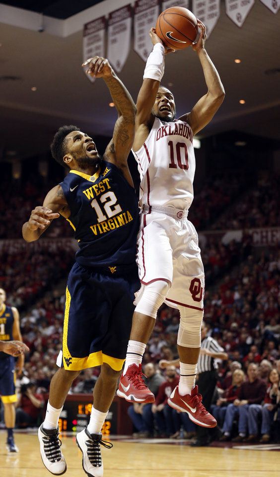 Photo - Oklahoma's Jordan Woodard (10) rebounds in front of West Virginia's Tarik Phillip (12) as the University of Oklahoma Sooner (OU) men play the West Virginia Mountaineers (WV) in NCAA, college basketball at The Lloyd Noble Center on Jan. 16, 2016 in Norman, Okla. Photo by Steve Sisney, The Oklahoman