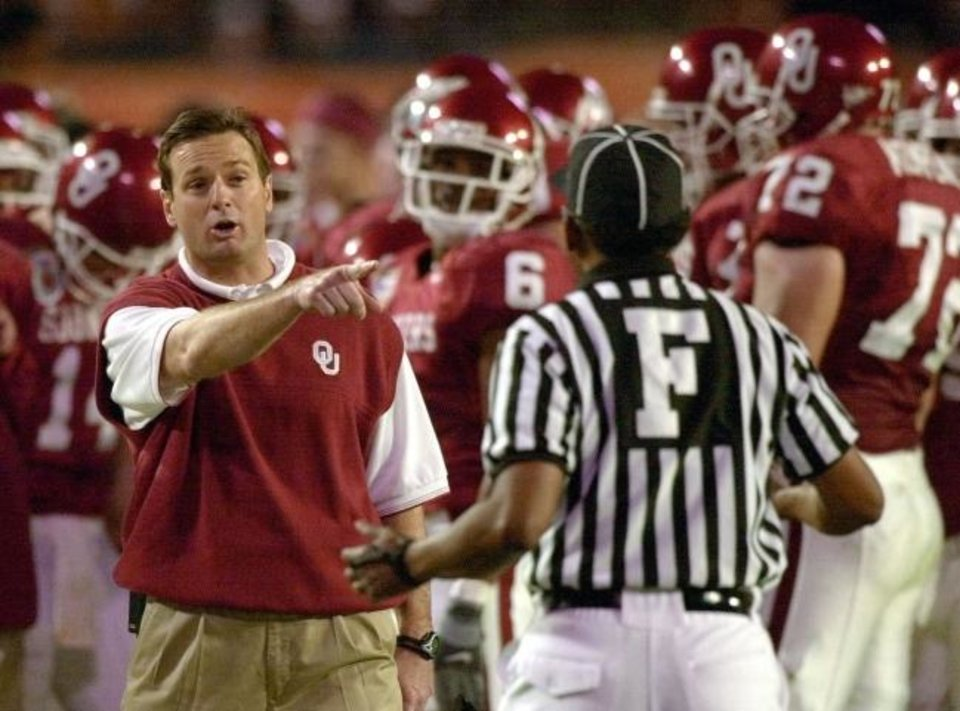 Photo -  Oklahoma coach Bob Stoops, left, argues a call with an official during a 13-2 win in the Orange Bowl agianst Florida State on Jan. 3, 2001. [AP Photo/Chris O'Meara]